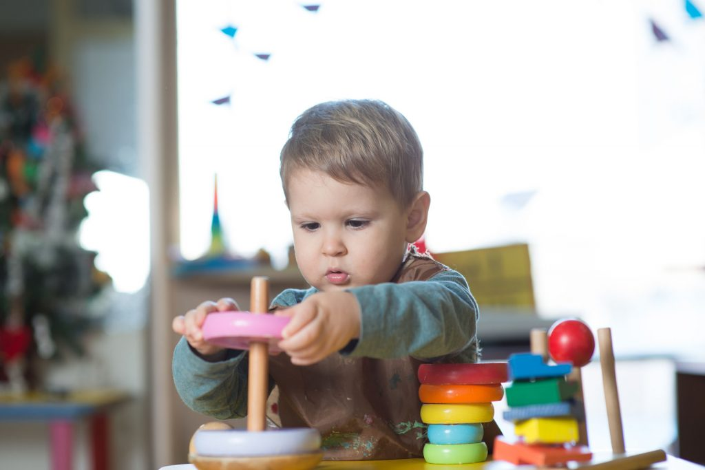 Little caucasian boy playing with Montessori toy in pre-school