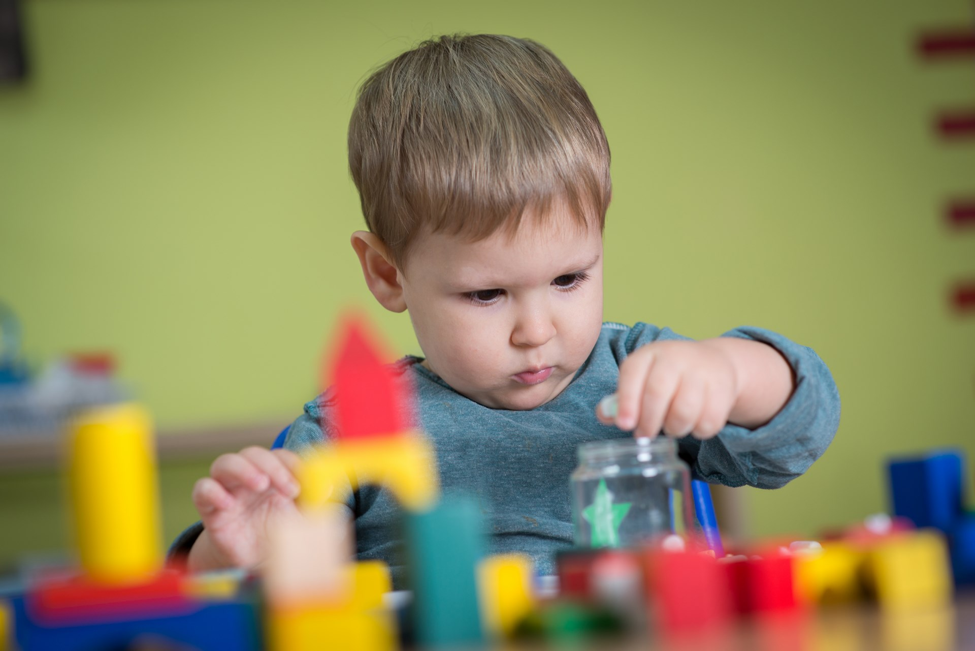 Kid is playing with toys in nursery